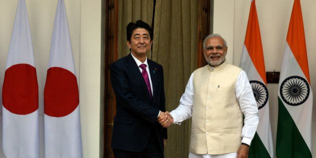 India's Prime Minister Narendra Modi (R) shakes hands with Japan's Prime Minister Shinzo Abe before a...