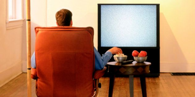 Rear view of a man sitting in an armchair and watching