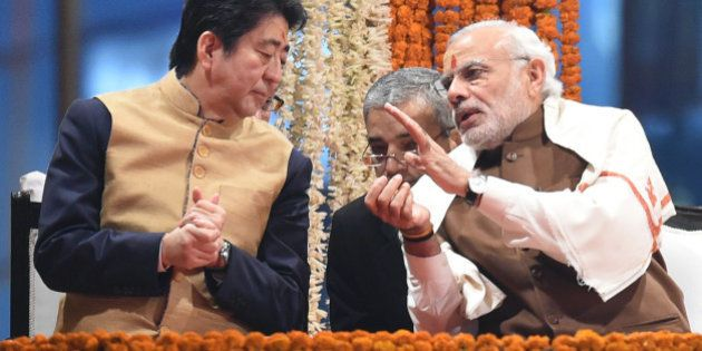 Japan's Prime Minister Shinzo Abe (L) and India's Prime Minister Narendra Modi (R) talk as they watch the evening 'Aarti' ritual on the banks of the River Ganges at Varanasi on December 12, 2015. Japan will build India's first bullet train under a sweeping tally of agreements made following talks in New Delhi on December 12, deepening a partnership Prime Minister Narendra Modi said would 'shape the course of Asia'.  Later the two leaders visited the Indian premier's parliamentary constituency of Varanasi, India's holiest city.  AFP PHOTO / PRAKASH SINGH / AFP / PRAKASH SINGH        (Photo credit should read PRAKASH SINGH/AFP/Getty Images)