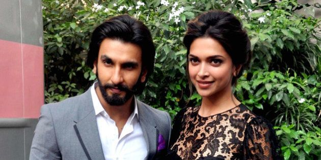 Indian Bollywood actor Ranveer Singh (L) poses with actress Deepika Padukone during a promotional event...