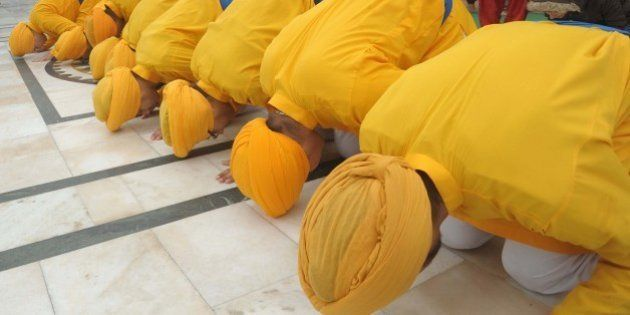 Young Sikhs pay their respects at The Golden Temple in Amritsar on December 27, 2014. A procession took...