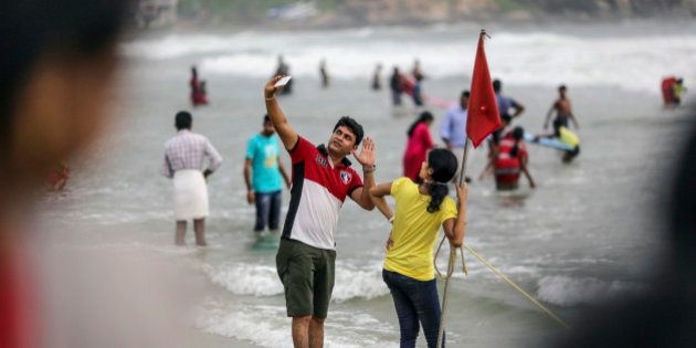 Visitors pose for a 'selfie' photograph at Kovalam beach in Kovalam, Kerala, India, on Sunday, May 31,...
