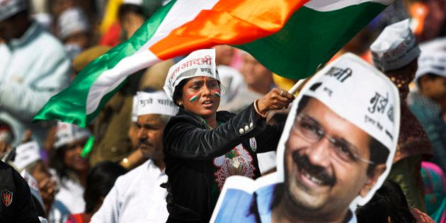 A supporter of Aam Aadmi Party, or Common Man's Party, waves an Indian flag next to a cut-out of party...