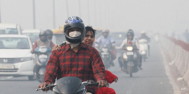 NEW DELHI, INDIA - NOVEMBER 13: Commuters drive past as roads were seen covered in smog, on November...