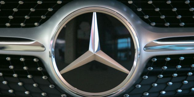 The Mercedes-Benz logo sits on a S-Class automobile in the center of excellence showroom at Daimler AG's...