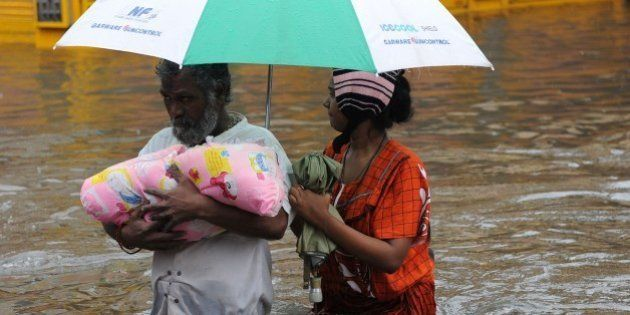 An Indian family wade through floodwaters in Chennai on December 2, 2015. India has deployed troops to...