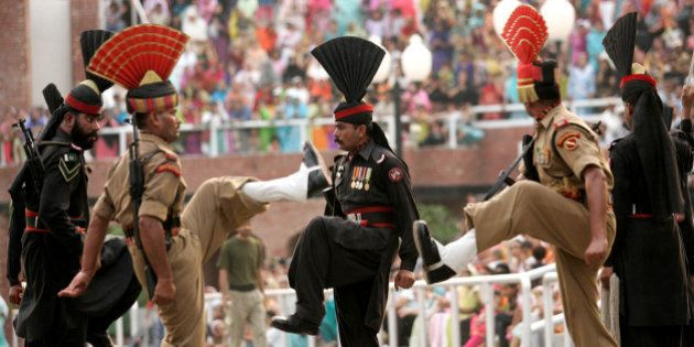 Indian Border Security Force soldiers and Pakistan Rangers soldiers, in black uniform, march during 'Beating...