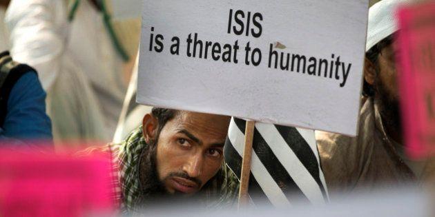 An Indian Muslim man holds a banner during a protest against ISIS, an Islamic State group, and Friday's...