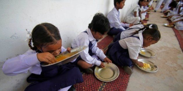An Indian schoolgirl drinks the gravy from a free midday meal at a government school on the outskirts...