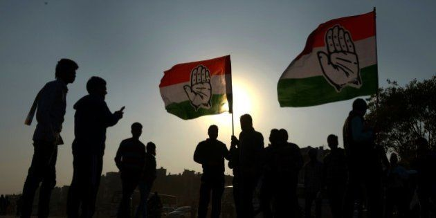 Supporters of the Congress party takes pictures with party flags after the election rally addressed by...