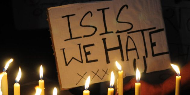 BHOPAL, INDIA - NOVEMBER 15: A Muslim kid holds a placard with slogan against the ISIS during a candle...