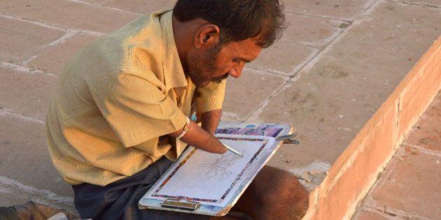 PUSHKAR, RAJASTHAN, INDIA - 2015/09/11: A handicapped artist, Bhagirath Sharma at Pushkar Ghat is painting...