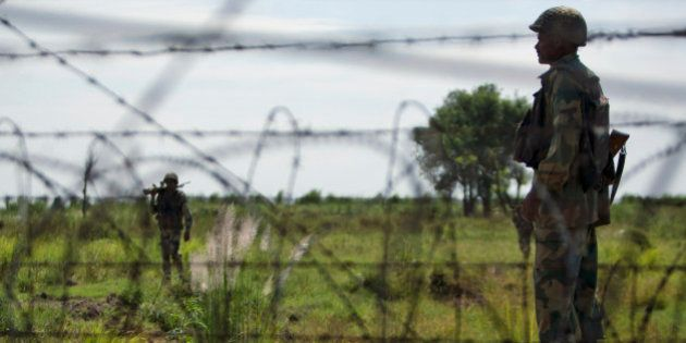 India's Border Security Force (BSF) soldiers patrol near the India-Pakistan international border fencing...