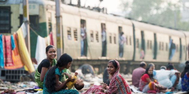 KOLKATA, INDIA - DECEMBER 12: Women take care of a baby in a slum on the railway tracks as a commuter...