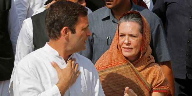 India's ruling Congress party President Sonia Gandhi, right, speaks with her son and party Vice President...