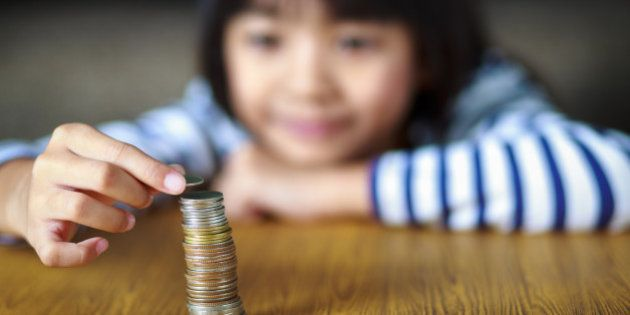 Little girl counts his coins on a table, select focus at