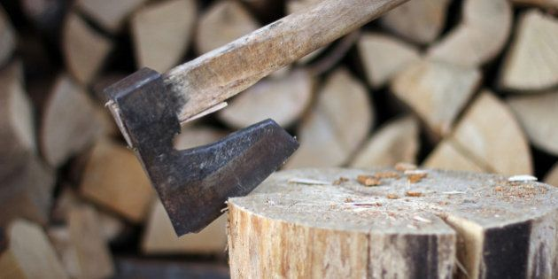 Old axe for chopping wood on wooden stump and chopped wood in the