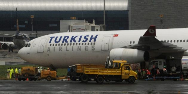 Indian airport authority officials gather for the recovery operation of the Turkish Airlines plane near...