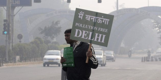 NOIDA, INDIA - JANUARY 1: A Civil Defence personnel holds a placard as he stands at a traffic intersection...