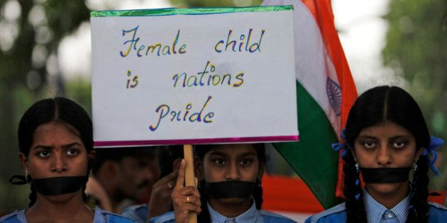 Indian schoolgirls hold a placard and participate in a silent rally against the rape of a 5-year-old...