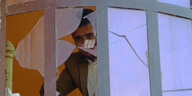 An Afghan man is seen through the shards of a broken window after a blast near the Indian consulate in...