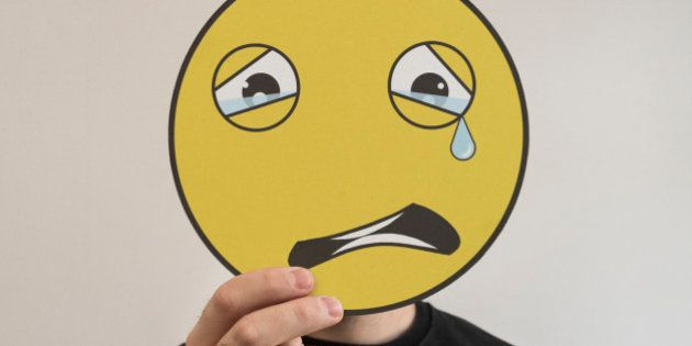 Man holding a crying emoticon face in front of his