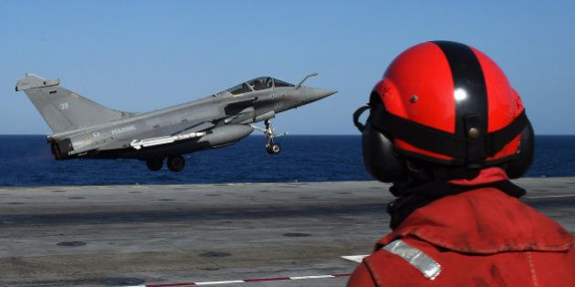 A French Rafale fighter aircraft carrying bombs is catapulted off French aircraft carrier Charles-de-Gaulle,...