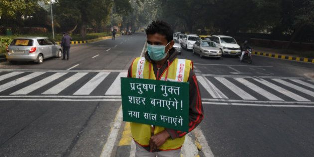 NEW DELHI, INDIA - JANUARY 4: A volunteer holds a placard for pollution free capital at APJ Kalam crossing...