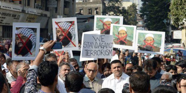 Indian activists carry photographs of the chief of Jaish-e-Mohammad, Maulana Masood Azhar (L) and chief...