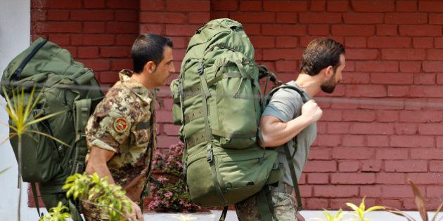 Italian marines, Massimiliano Latorre, left, and Salvatore Girone, walk with their backpacks towards...