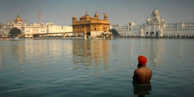 An Indian Sikh devotee takes a holy dip in the sacred pond at the Golden Temple in Amritsar, India, Wednesday,...