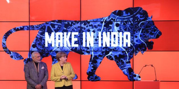 Angela Merkel, Germany's chancellor, right, and Narendra Modi, India's prime minister, stand on stage as a 'Make In India' logo is displayed at the Hanover industrial fair in Hanover, Germany, on Monday, April 13, 2015. Modi said 'huge' opportunities await German industry as he seeks to roll back barriers to foreign investment and speed up growth in Asia's third-biggest economy. Photographer: Krisztian Bocsi/Bloomberg via Getty Images