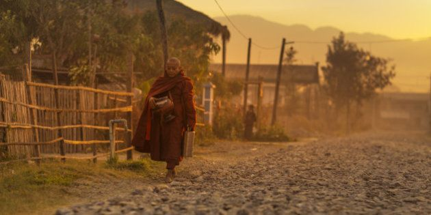 Buddhist monk goes from door to door to collect food and provide prayers in