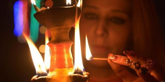 An Indian woman lights an earthen lamp in Amritsar on November 10, 2015 on the eve of the Indian festival...