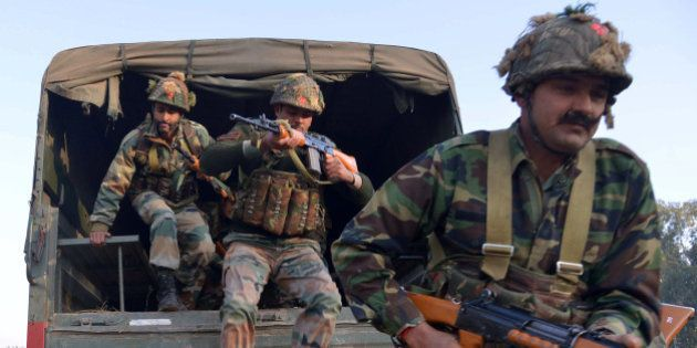 Indian army personnel leap from the rear of a truck at an airforce base in Pathankot on January 3, 2016,...