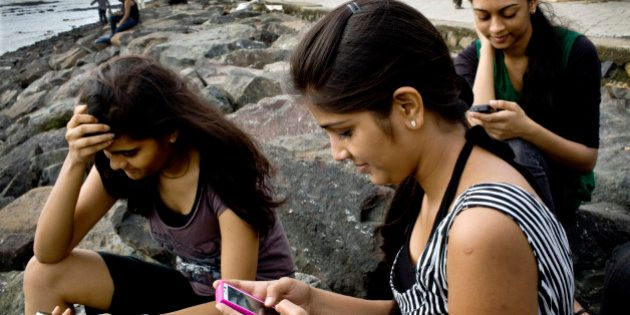 College students Saloni Shah, 18, from left, Roshani Munat, 18 and Shruti Jain, 19, check Facebook Inc....