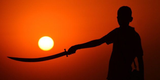 RAJASTHAN, INDIA - 2015/11/19: A child standing with a sword in hand during the sunset at the annual...