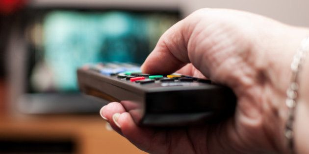 A close up of a woman's hand holding a TV remote control, pointing at the TV in the