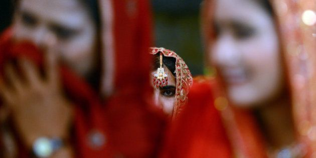 Pakistani brides attend a mass marriage ceremony in Karachi late March 26, 2013. Some 110 couples participated...