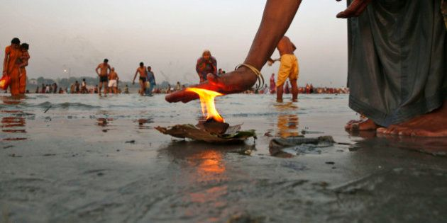 An Indian Hindu devotee offers prayers with a lamp, as others take holy dips at Sangam, the confluence...