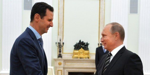 Russian President Vladimir Putin (R) shakes hands with his Syrian counterpart Bashar al-Assad (L) during...