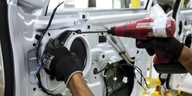An employee uses a drill to fit a speaker to the door of a Mahindra & Mahindra Ltd. XUV 500 sport-utility...