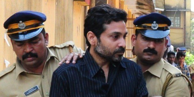 Indian police personnel escort murder suspect Muhammad Nisham (C), accused of fatally wounding a security...