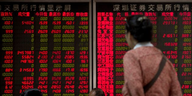 Chinese investors chat while monitoring stock prices at a brokerage house in Beijing Monday, July 13,...