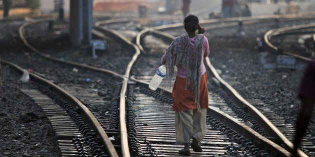 An Indian woman walks after defecating on a railway track, on World Toilet Day in Gauhati, India, Wednesday,...