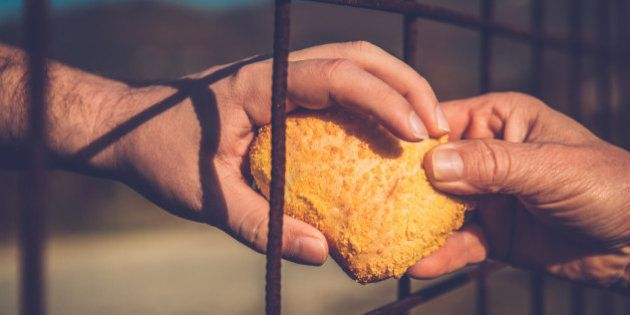 Person gives an immigrant a bread through the fence, border, hands only