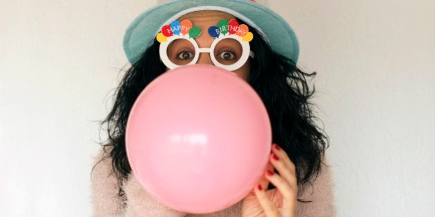 Young woman with birthday hat and birthday glasses, blowing pink balloon. White