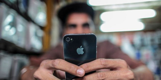 A man operates a Apple Inc. iPhone at a mobile phone store in this arranged photograph in Mumbai, India,...