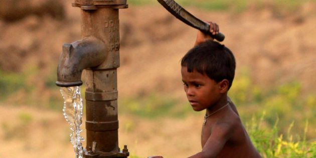 A young Indian boy pumps water from a tube well and stretches to fill a bottle with water, on the outskirts...