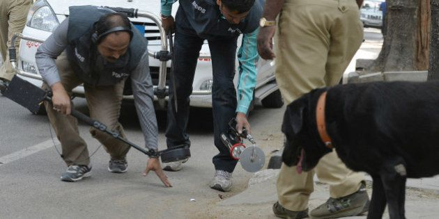 Indian bomb-disposal personnel and police sniffer dogs search an area where an unidentified package was...